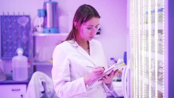 Žena vědec zapisování poznámek v laboratoři