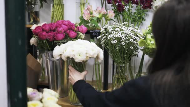 Woman Florist Putting Vases With Flowers On Shop Shelves Stock