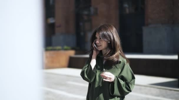 Pretty girl in a green shirt talking on the phone in the street, front view