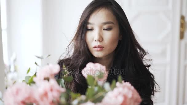 Mladá asijská žena s růžová kytice ve váze doma