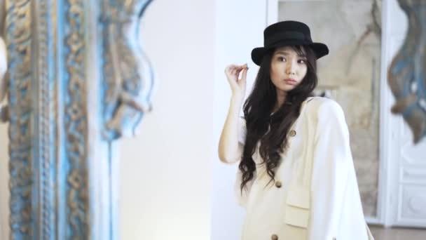 Ázsiai nő, egy kalap van kipróbálás egy kabát, egy bolt