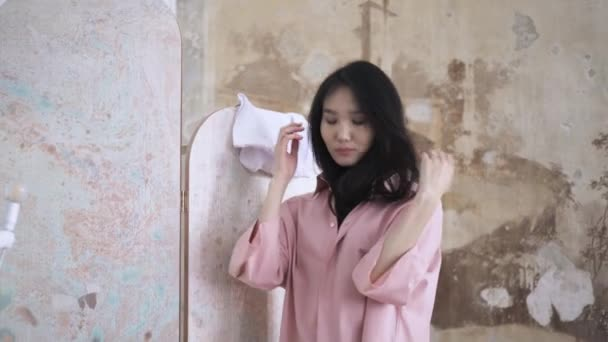 asiatische Frau in weißen Jeans probiert in einem Geschäft ein breites rosa Hemd an