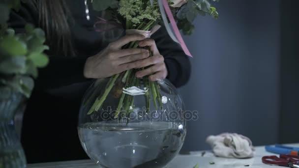 Zblízka žena s rukou uvedení krásné kytice květin ve váze