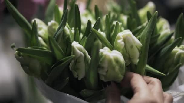 Květinářství shop zaměstnanec uspořádání kytice zelenobílá