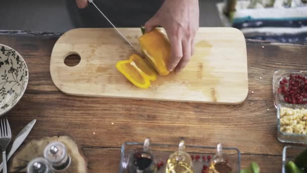Top view of a chef slicing a yellow bell pepper and putting it in a bowl