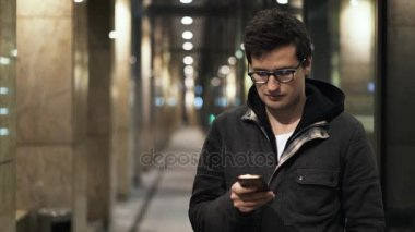 Young man texting in the street in the evening