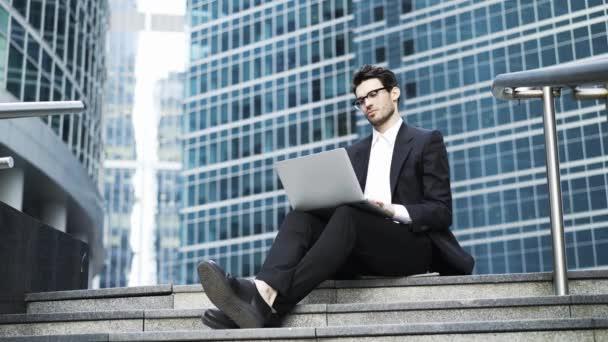 Boční pohled pohledný mladý podnikatel pracuje s notebookem venku