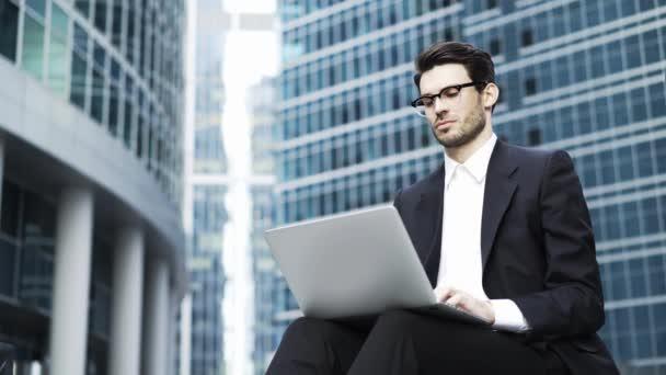 Egy jóképű fiatal üzletember dolgozik a laptop kívül közelről