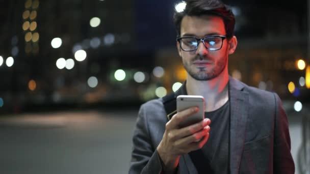 junger Geschäftsmann zu Fuß in einer Nacht Straße und Web-Surfen aus nächster Nähe