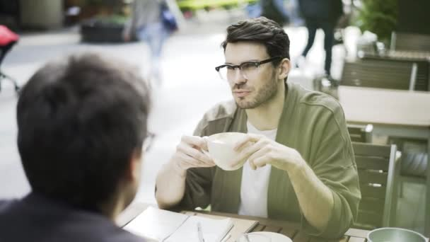 Young hipster guy in glasses in a cafe talking to his friend