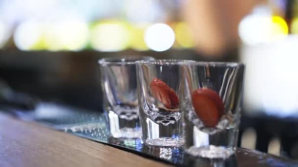 Zblízka barman nalil vodku do koktejlových sklenic s jahodou