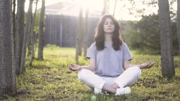 Egy fiatal nő, egy parkban meditál elölnézete