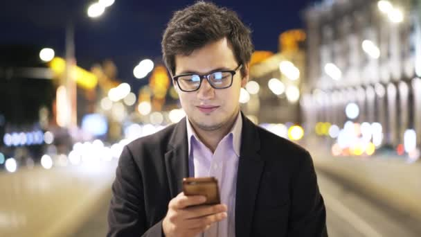 Handsome young businessman in glasses web surfing and smiling, smartphone, night