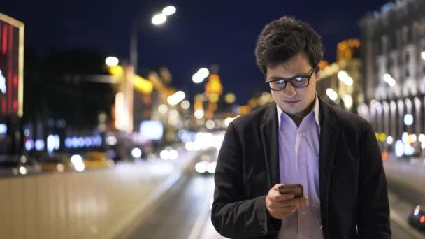 Čelní pohled atraktivní mladý podnikatel pomocí svého mobilního telefonu v noční město