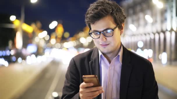 Handsome young businessman in glasses web surfing with phone at night outside