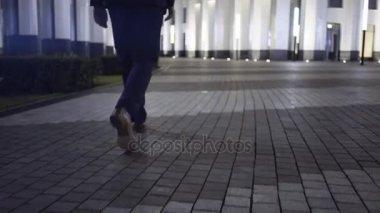 Man s legs walking in a night city downtown