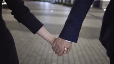 Young couple of business people walking in a night city holding hands, close up