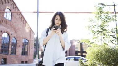 Serious dark haired walking and web surfing from her smartphone