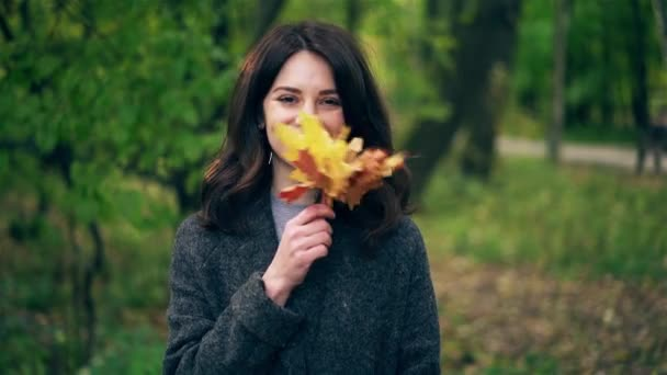Young woman waving maple leaves near her face in autumn park