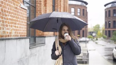 Woman under umbrella drinking coffee