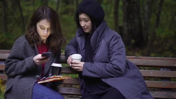 Two beautiful young women with a smartphone in a park
