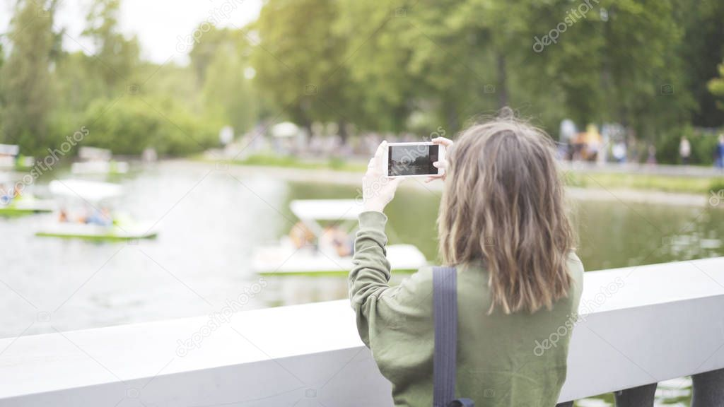 A girl taking a photo of the park