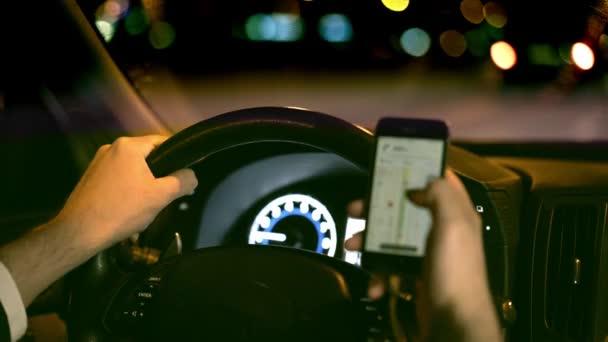 Mann fährt nachts Auto und surft im Internet