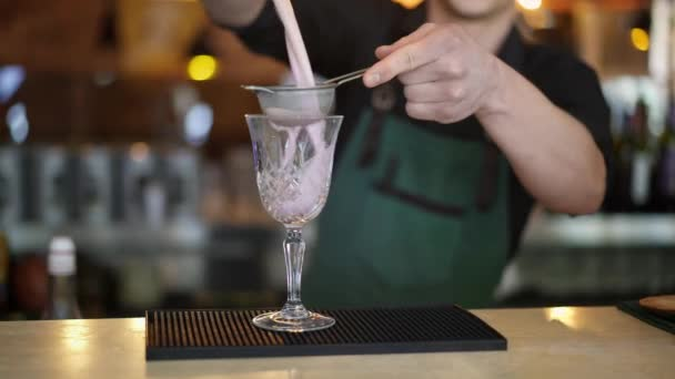 Bartender pouring pink cocktail in crystal glass holding a strainer