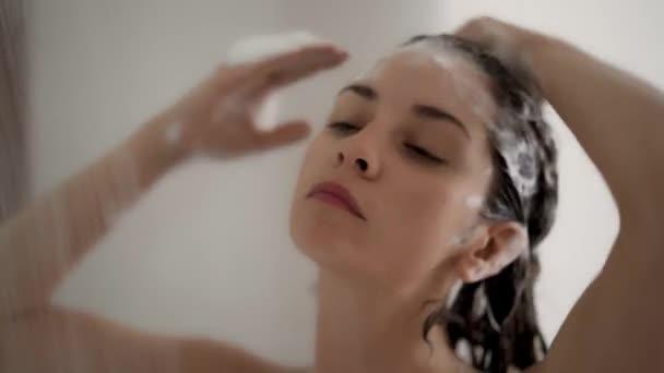 Nahaufnahme einer Frau, die sich unter der Dusche mit Shampoo die Haare wäscht
