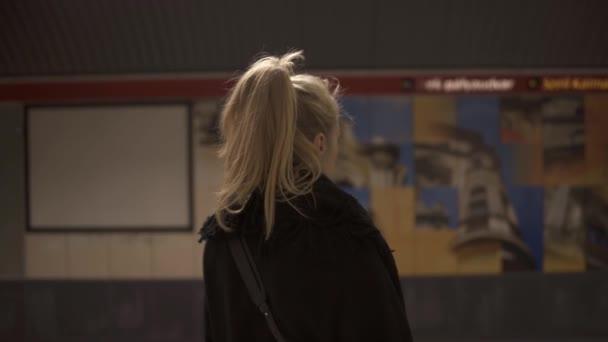 Kézzel fogható hátsó lövés egy szőke nő áll a metró peronon