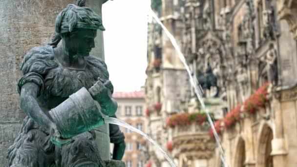Echtzeit-Medium-Aufnahme der Figur eines Jungen am berühmten Fischbrunnen am Marienplatz in München, Deutschland.