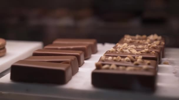 Zoom out of several chocolate small cakes behind the glass