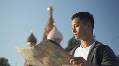 Portrait shot of a young Asian man looking at map. The Cathedral of Vasily the Blessed on background, Moscow Russia. Red Square area.