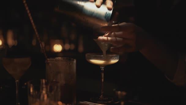Handheld real time close up shot of a bartender preparing a cocktail at a bar in Bangkok, Thailand. Nightlife of a big city