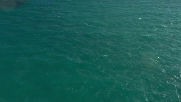 Drohnen fliegen über azurblaue Wellen und Sandstrand, keine Menschen