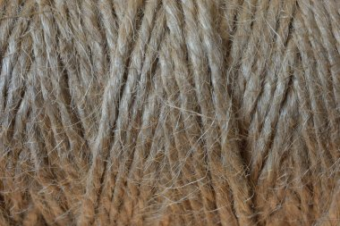 A close up image of a spool of brown jute thread.