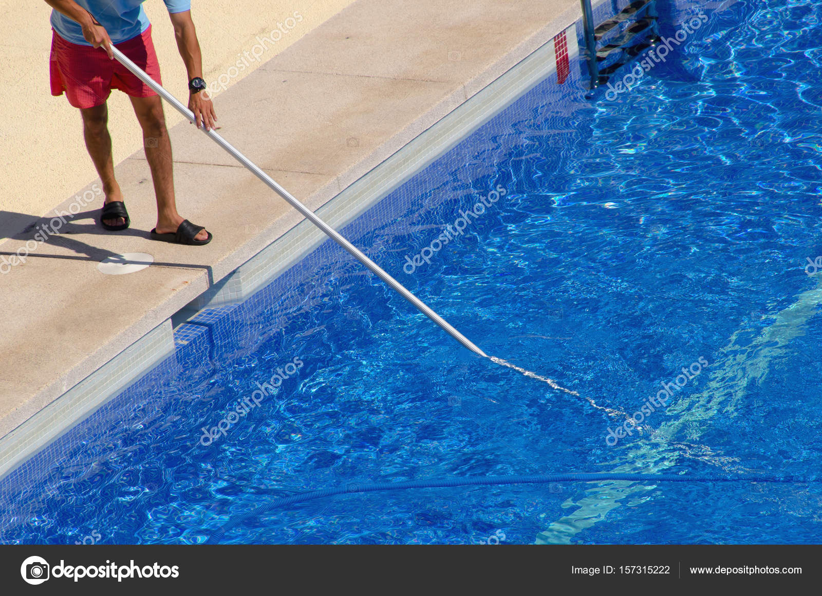 Guy cleaning the swimming pool with a brush from the ...