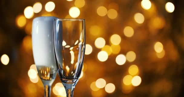 Champagne is poured into glasses against the background of New Year s garland.