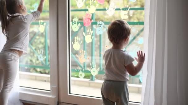 Děti malují dlaněmi na okno. Karanténa