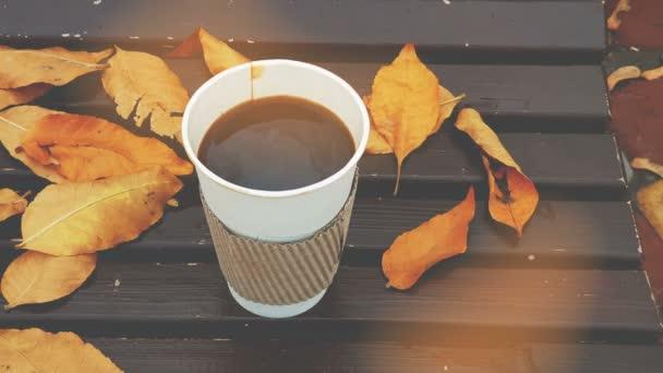 Kávu s sebou. Káva s sebou na lavici s žluté listí v podzimním parku. 4k videa. Tónovat je kino účinky.