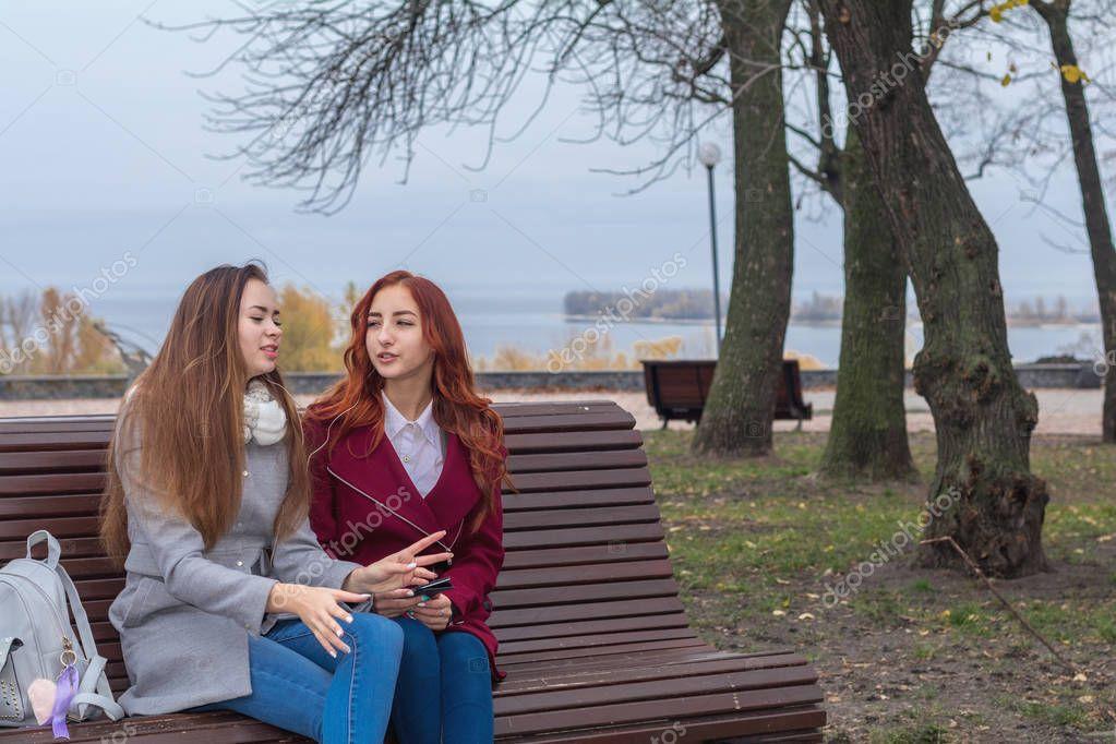 Female teenagers listening to music on smartphone sitting