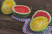 Cut red and yellow watermelons on a wooden box in a vintage wood