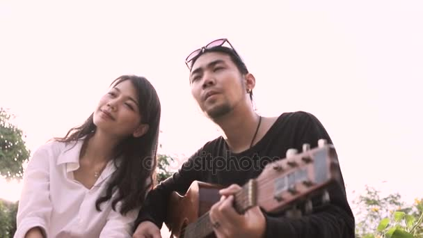 asian younger  man and woman relaxing emotion playing guitar outdoor