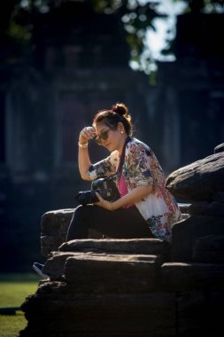 woman tourist with dslr camera in hand sitting on rock with beau