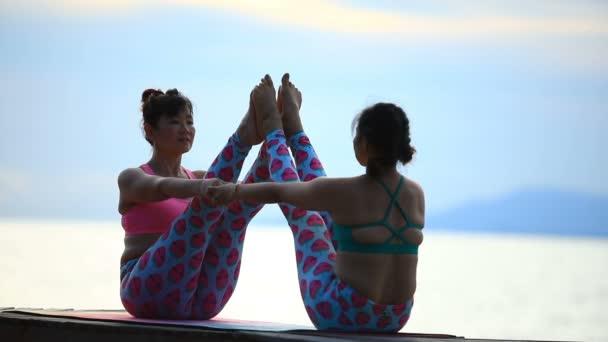 zwei asiatische Frau spielen Yoga auf Meer Seite