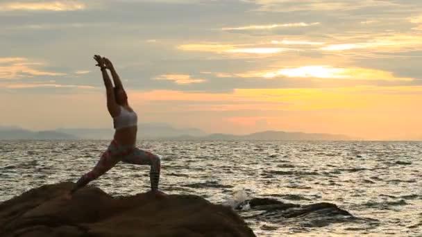 nő játszik a jóga a tengeren oldalán emelkedik az ég gyönyörű nap