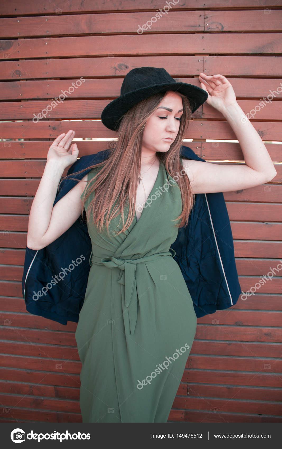 ffe9d9c63bf3 Giovane bella ragazza in un cappello nero e vestito lungo su un fondo di  legno marrone — Foto di ponagar87 gmail.com
