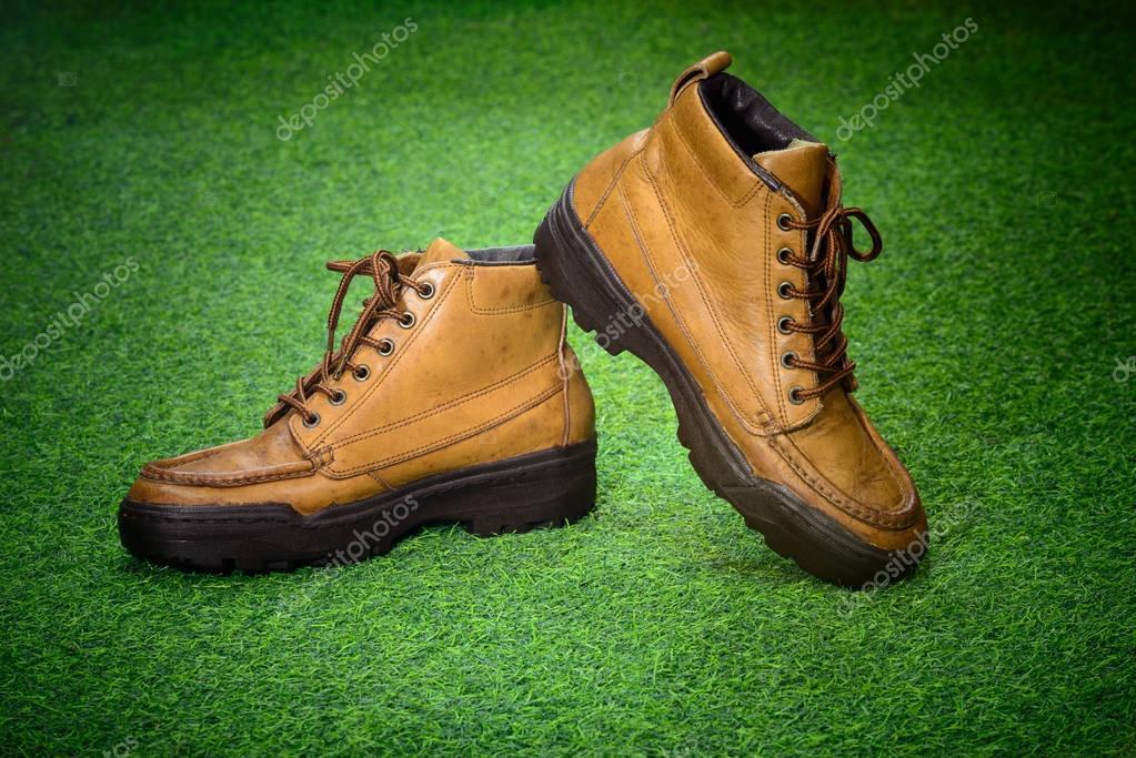 be575f7907 Obuv pro muže - 2 strany hnědá pravá kůže retro boty adventure stylově na  zelenou trávu pozadí — Fotografie od ...