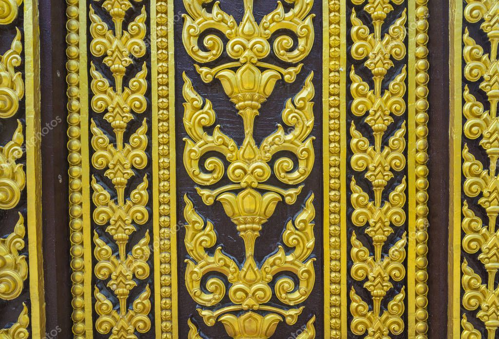Temple door decorated with gold leaf designs Thailand