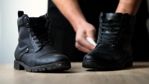 ein Mann, der schmutzige Stiefel mit einem weißen Lappen reinigt